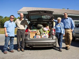 Fall Mountain Food Shelf director, Mary Lou Huffling and Bensonwood events committee members, (L to R) Jeffery Starratt, Kevin Bittenbender, and Erik Walker, next to a carload of donated food.